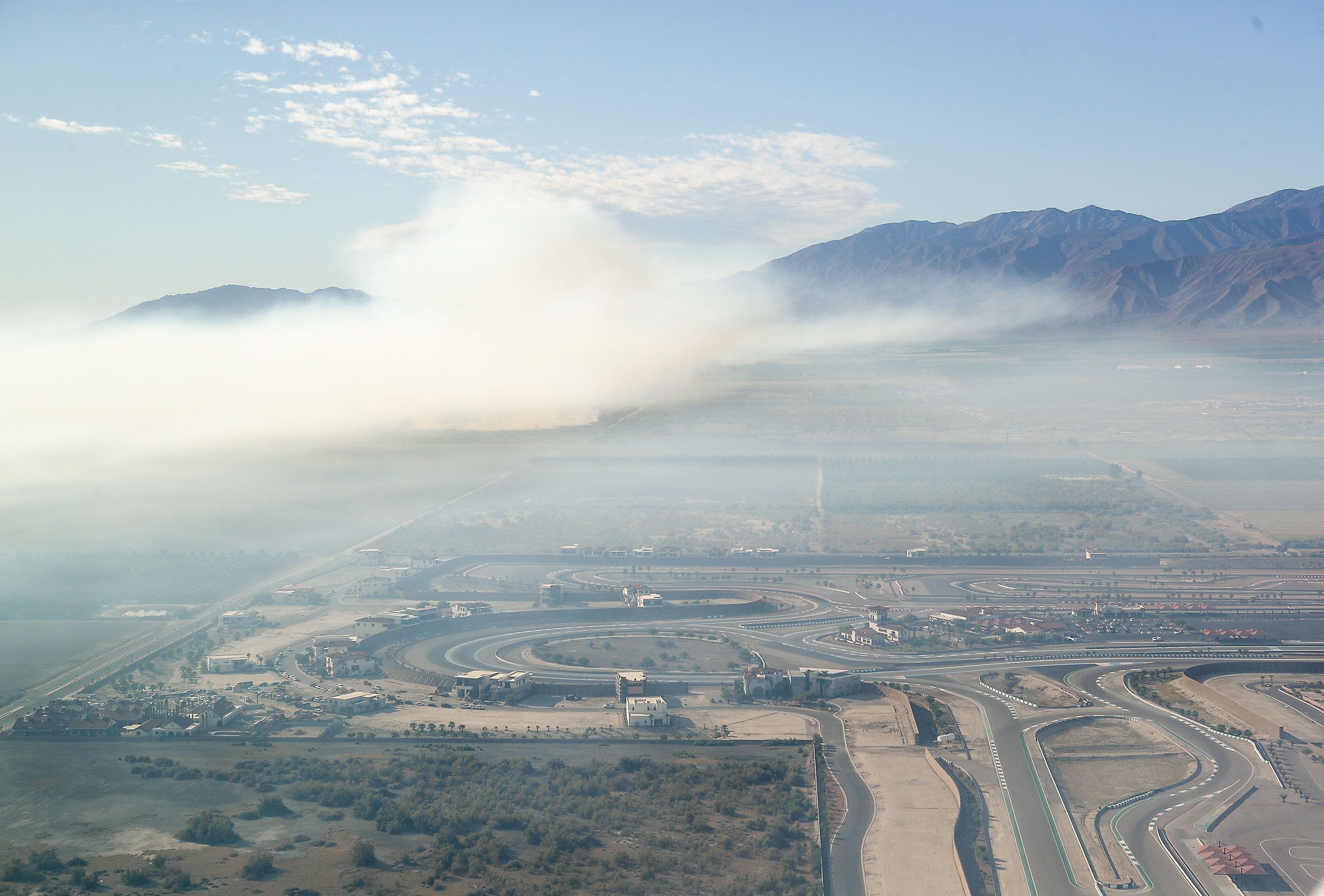 Smoke from the dump fire in Thermal, Calif., pollutes the air just a short distance from The Thermal Club race track (lower right) in this aerial photo, October 17, 2019.