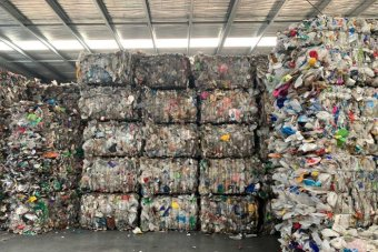 A picture of seven rows of recycling rubbing, stacked into squares and piled to a warehouse ceiling.