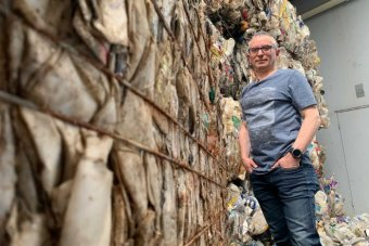 A picture of a man with grey hair and glasses, standing in jeans and a t-shirt and surrounded by piles of rubbish.