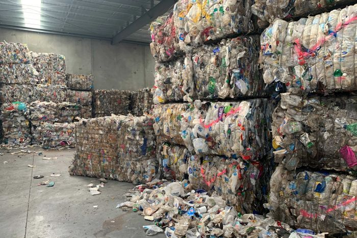 A picture of rubbish packaged into squares and piled all through a grey warehouse. Loose rubbish can be seen on the ground.