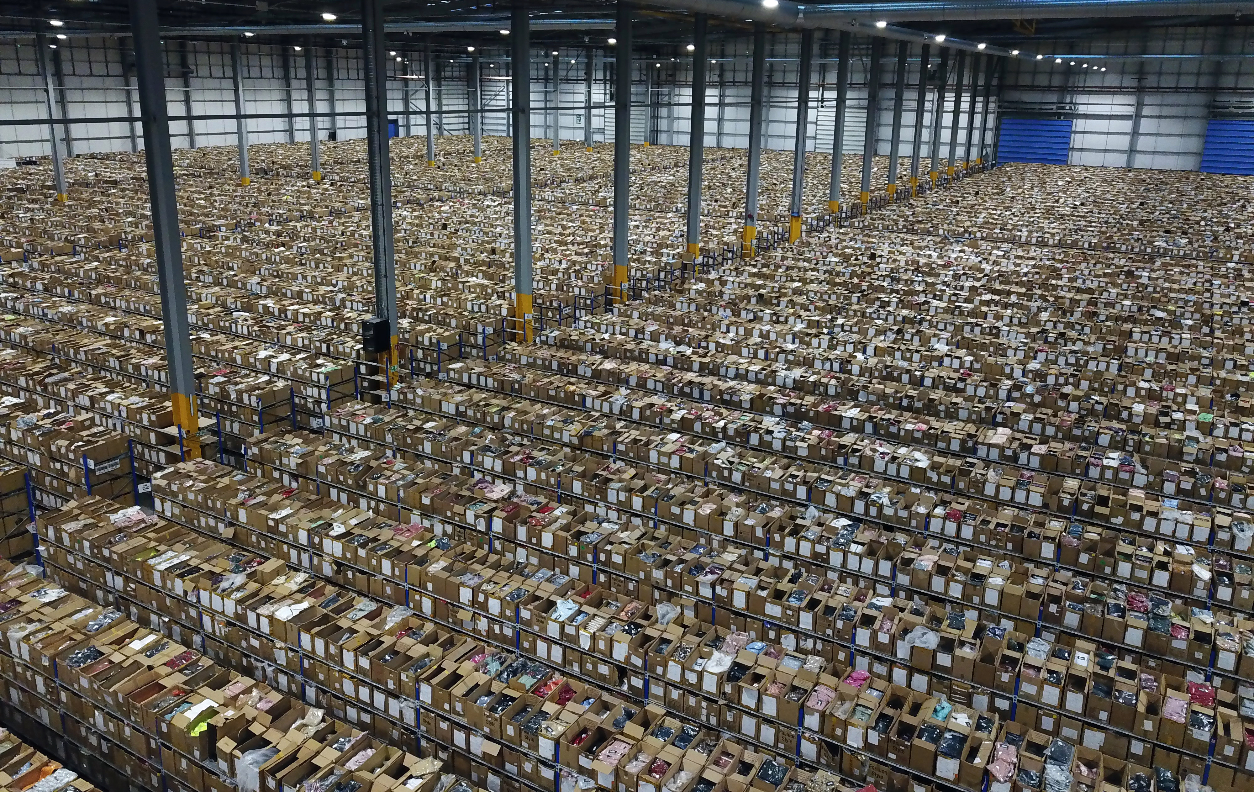 A startling picture from inside the mega-warehouse of clothing brand PrettyLittleThing — the size of 15 football pitches — showing 3,000 workers piling a million orders into boxes ahead of the Black Friday sale